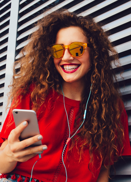 Smiling woman listening to music on a cell phone