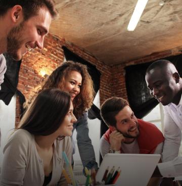 Três homens e duas mulheres em torno de um laptop