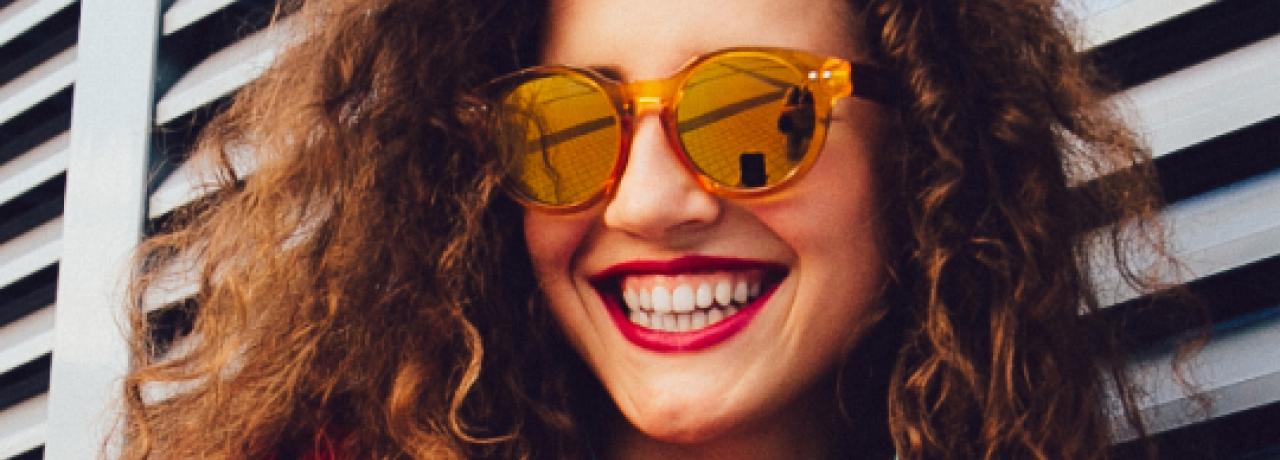 Mujer sonriente escuchando música en un teléfono celular